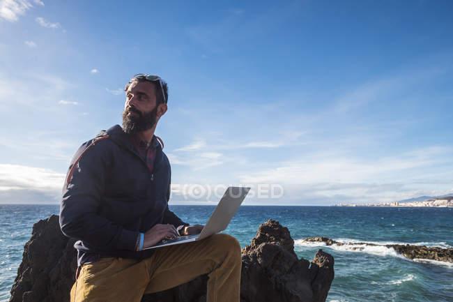 Ritratto dell'uomo con computer portatile seduto sulla roccia di fronte al mare — Foto stock