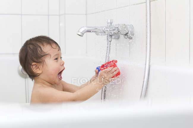 Baby girl playing with toy in a tub — Stock Photo