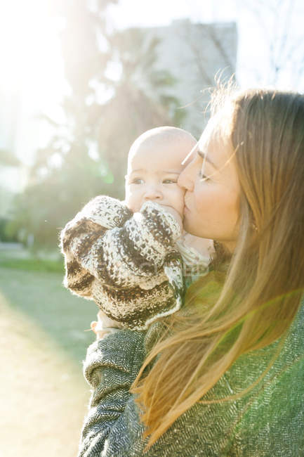 Portrait of young woman kissing baby boy — Stock Photo