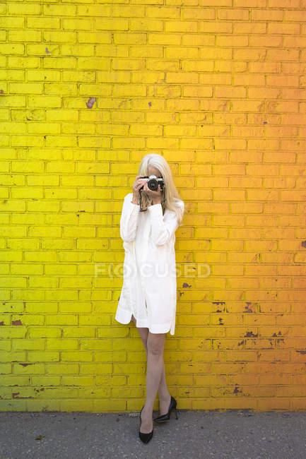 Porträt einer Seniorin beim Fotografieren in der Nähe einer orangefarbenen Wand — Stockfoto