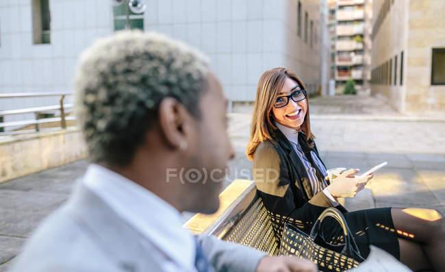 Jovem empresário e mulher sentados no banco da cidade — Fotografia de Stock