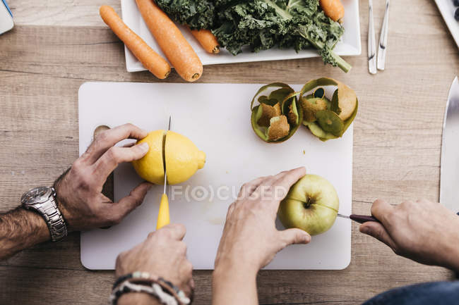 Manos cortar frutas - foto de stock