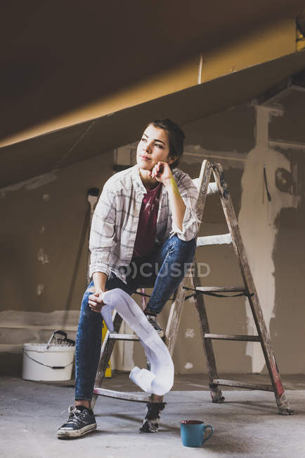 Portrait of young woman sitting on ladder — Stock Photo
