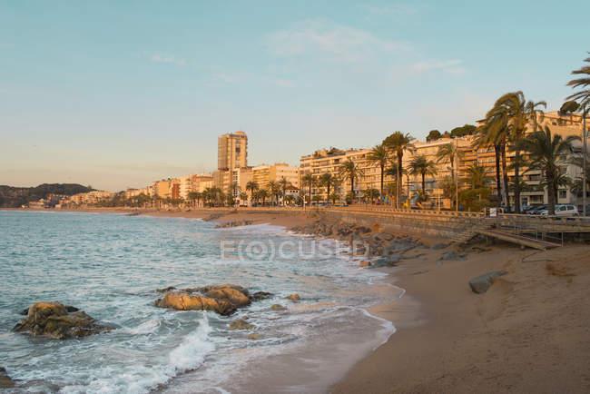 Spain, Costa Brava, Lloret de Mar, buildings on beach promenade at sunrise — Stock Photo