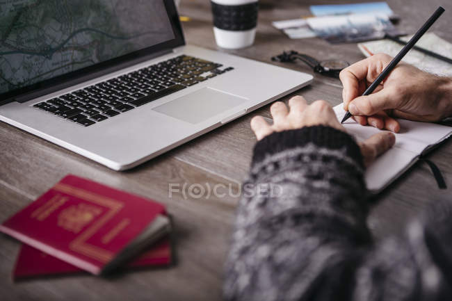 Man writing in notebook at table with laptop — Stock Photo