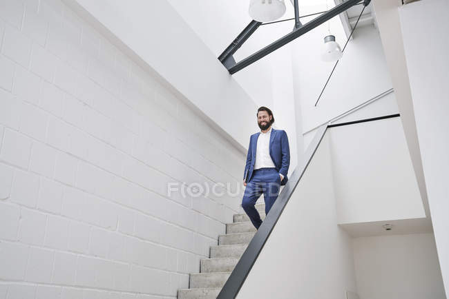 Lächelnde Geschäftsmann zu Fuß im Erdgeschoss, im Bürogebäude — Stockfoto