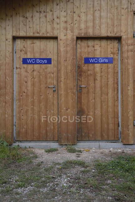 Deux portes de toilettes en bois pour garçons et filles — Photo de stock