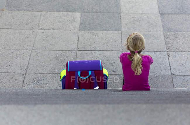 Menina com bolsa escola, sentado na escada — Fotografia de Stock