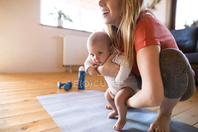 Улыбающаяся мать с ребенком и гантели дома — стоковое фото