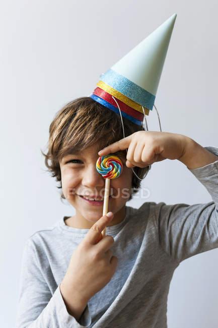 Портрет мальчика в шляпах для вечеринок, закрывающего глаза леденцом — стоковое фото