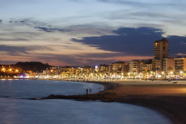 Spain, Catalonia, Lloret de Mar, resort town on Costa Brava, beach and skyline at twilight — Stock Photo