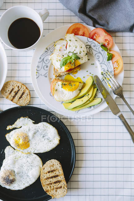 Closeup view of fried eggs with toasts and sliced tomato — Stock Photo