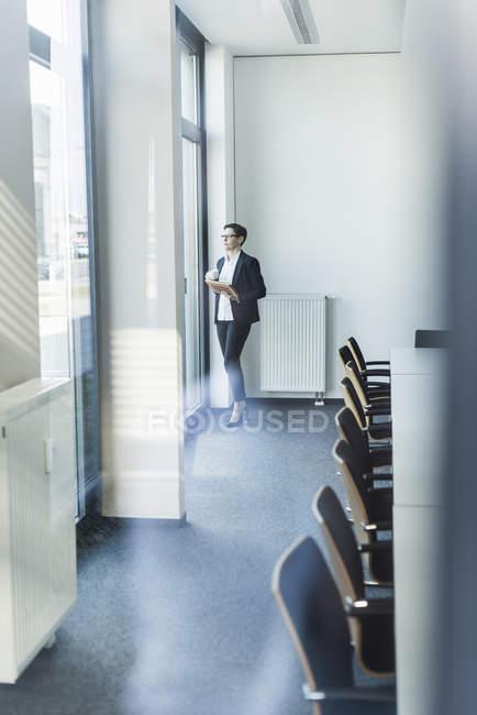 Retrato de mujer de negocios madura de pie cerca de la ventana en la oficina - foto de stock