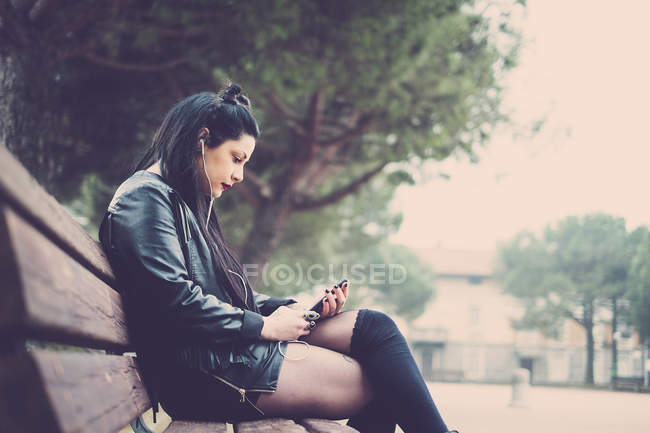 Dark-haired young woman sitting on bench and listening music with earphones and smartphone — Stock Photo