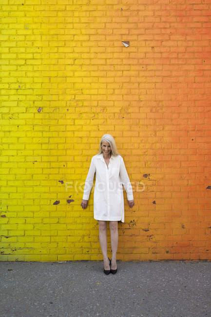 Porträt einer Seniorin, die in der Nähe orangefarbener Ziegelmauer steht — Stockfoto