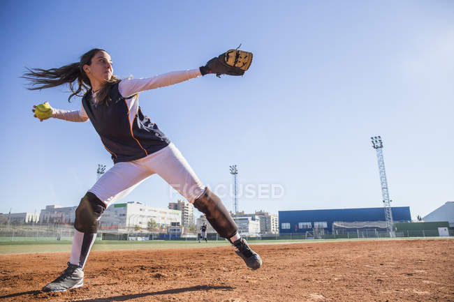 Female baseball player throwing the ball during a baseball game — Stock Photo