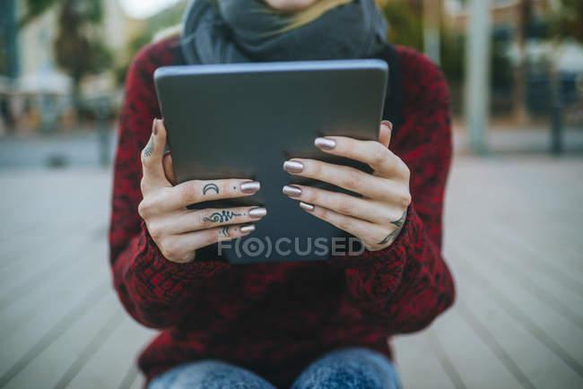 Primo piano delle mani femminili tatuate con tablet sulla strada — Foto stock