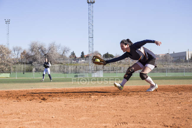 Female baseball player catching the ball during a baseball game — Stock Photo