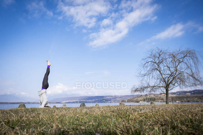 Woman practicing yoga doing a headstand at lake — Stock Photo