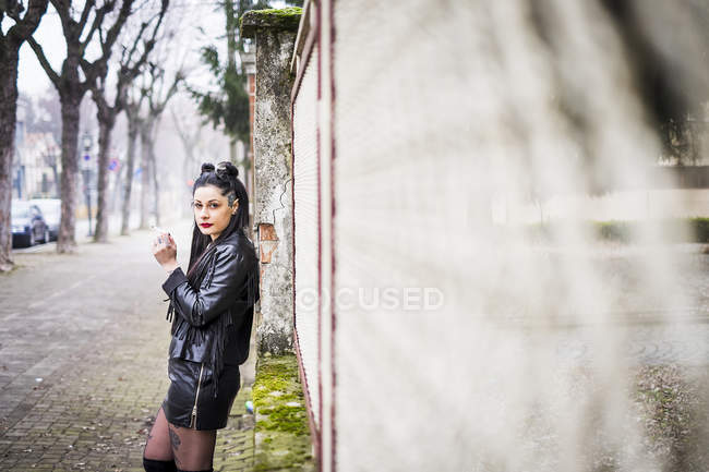 Dark-haired young woman dressed in black smoking cigarette — Stock Photo