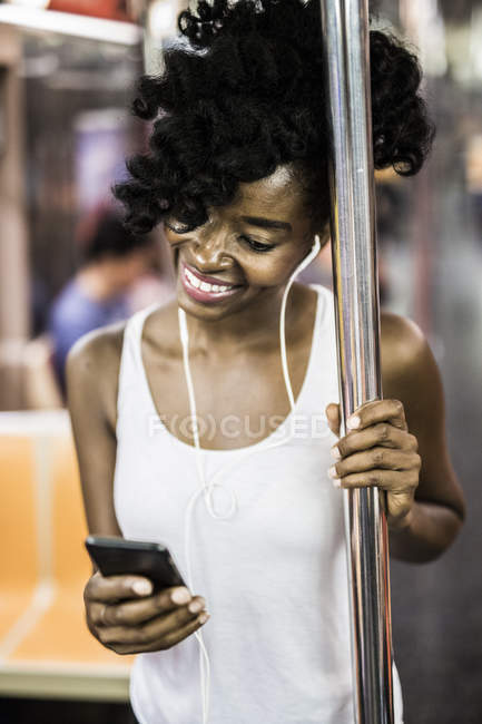 Portrait of woman using smartphone in subway — Stock Photo