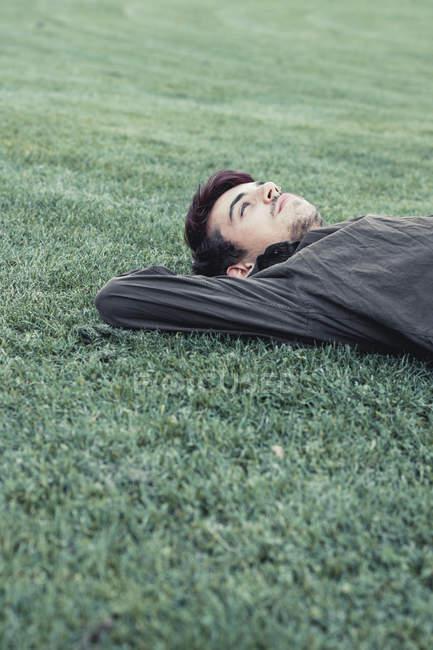 Rêver jeune homme allongé sur la pelouse — Photo de stock