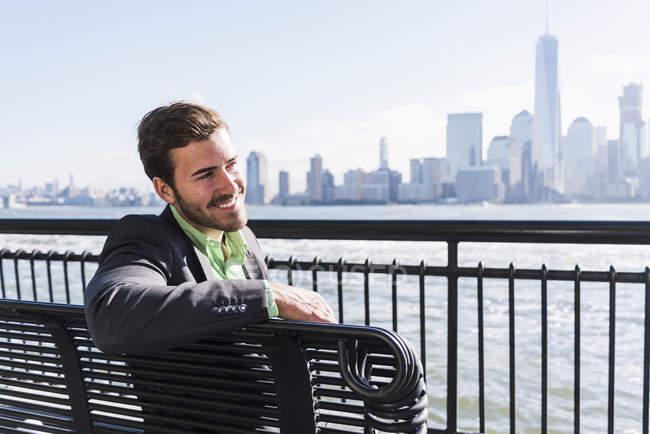 Uomo sorridente seduto sulla panchina del lungomare del New Jersey con vista su Manhattan, USA — Foto stock