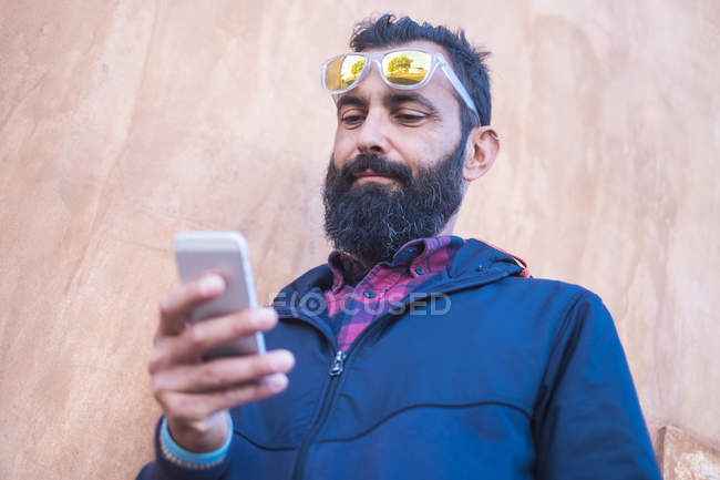 Portrait of man with full beard using cell phone in front of beige wall — Stock Photo