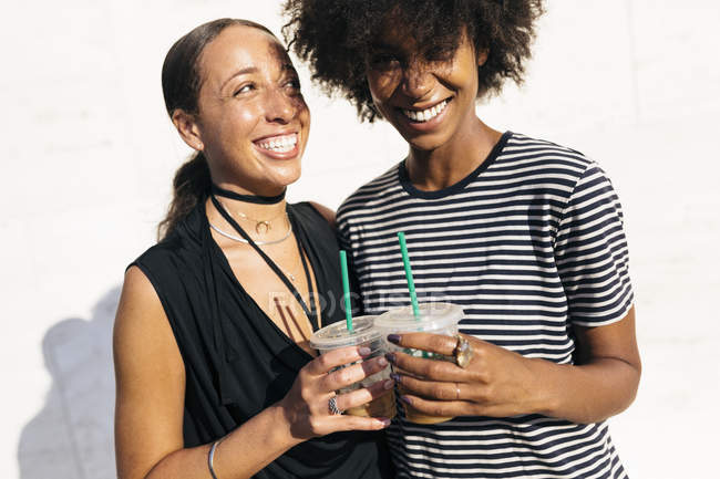 Two laughing women toasting with drinks in plastic cups — Stock Photo