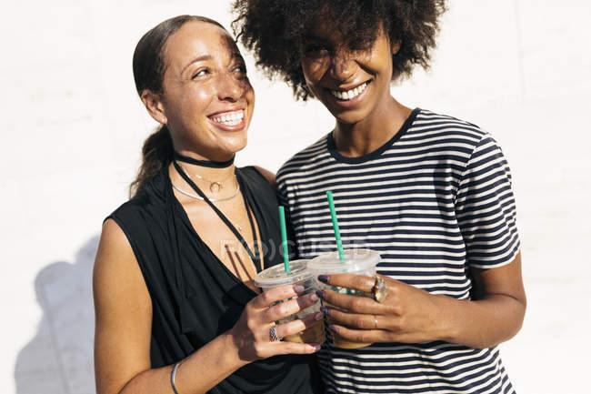 Duas mulheres rindo, brindando com bebidas em copos de plástico — Fotografia de Stock