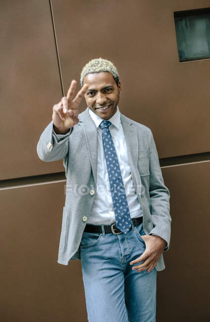 Businessman standing in front of wall and showing peace sign — Stock Photo