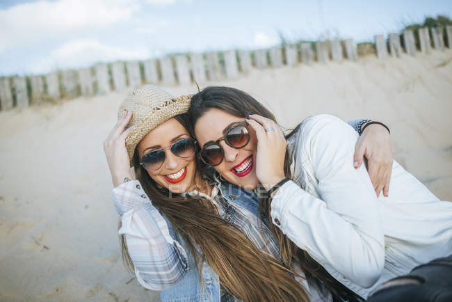 Retrato de duas jovens mulheres abraçando e sorrindo na praia na Espanha, Andaluzia, Vejer de la Frontera — Fotografia de Stock