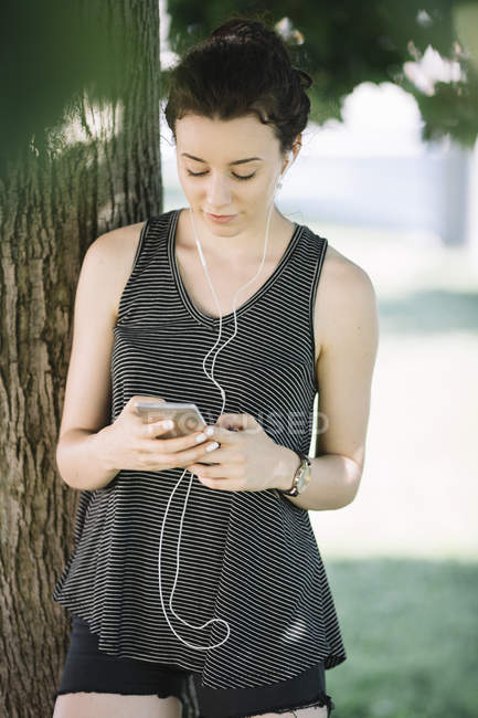 Young woman listening music with earphones in summer — Stock Photo