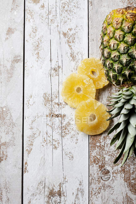 Top cropped view of whole and sliced dry pineapple on shabby wooden planks — Stock Photo
