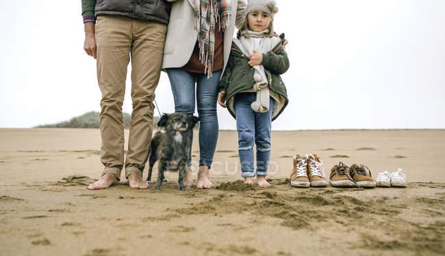 Menina olhando para a câmera enquanto estava descalça com sua família sobre a areia da praia ao lado de seu calçado — Fotografia de Stock