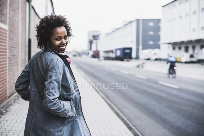 Улыбающаяся молодая женщина на тротуаре смотрит в камеру — стоковое фото