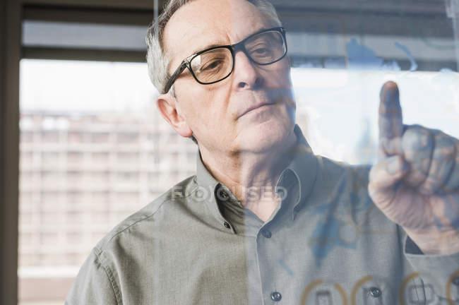 Abgeschnittenes Porträt eines Geschäftsmannes, der Glasscheibe berührt — Stockfoto