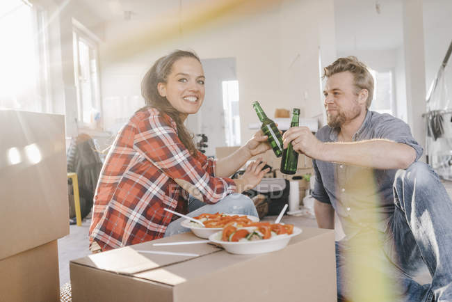 Couple eating salad and drinking beer in new home — Stock Photo