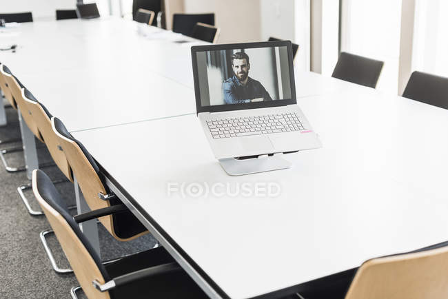 Portrait of businessman image on laptop screen — Stock Photo