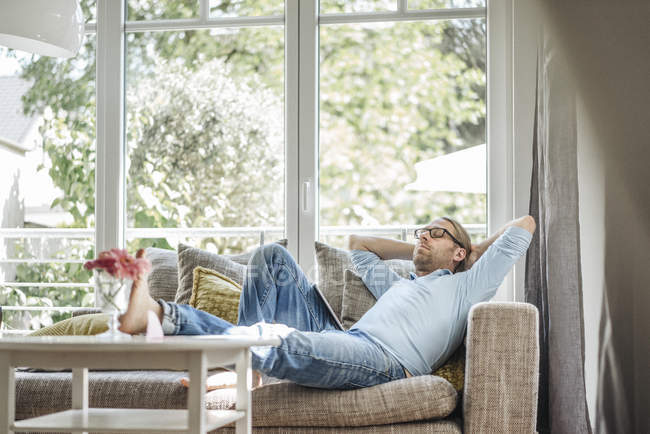 Tired man relaxing on couch at home — Stock Photo