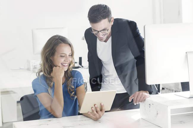 Jeune homme et jeune femme travaillant ensemble au bureau — Photo de stock