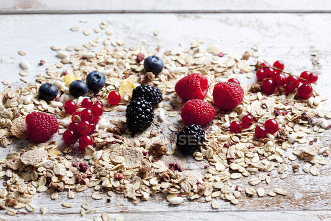 Closeup view of different berries with oat flakes on wood — Stock Photo