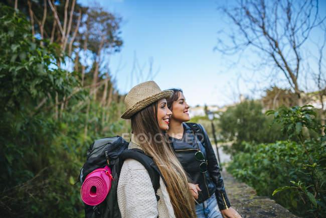 Traveling women walking on leafy path — Stock Photo