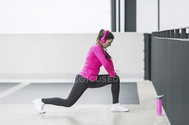 Woman in headphones warming up before jogging outdoors — Stock Photo