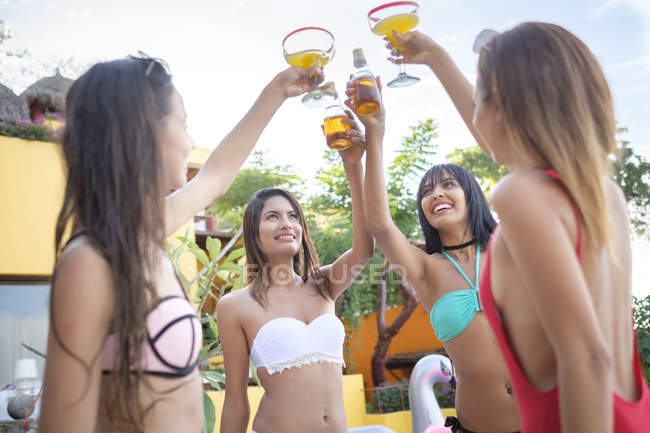 Four young women clinking cocktail glasses and beer bottles in a resort — Stock Photo