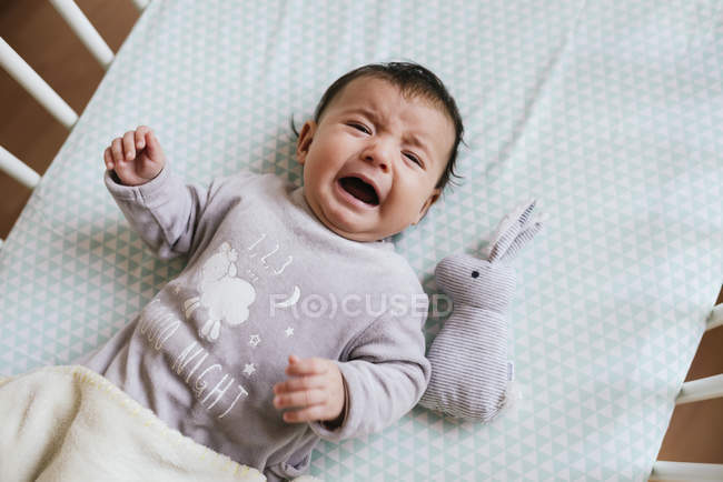 Baby girl crying in bed with stuffed rabbit — Stock Photo