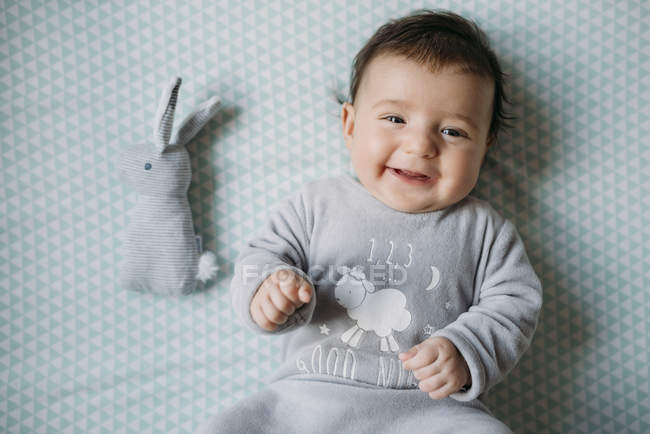 Happy smiling girl lying in a crib with stuffed rabbit — Stock Photo