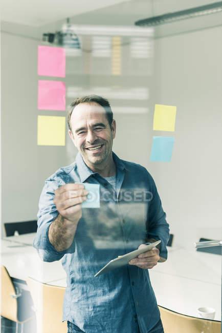 Портрет зрелых улыбаясь бизнесмена, наклеивания бумаги — стоковое фото