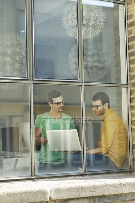 Junge Berufstätige am Fenster mit Laptop — Stockfoto