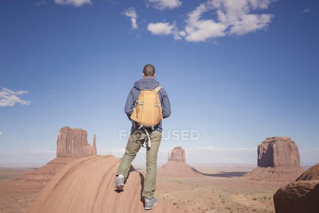 USA, utah, ein Mann mit Rucksack blickt auf das Tal des Denkmals — Stockfoto